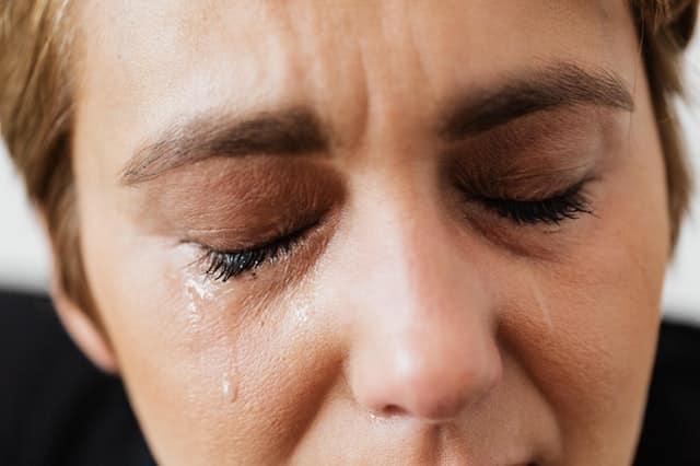 Mulher vista de perto com lágrimas escorrendo do rosto de olhos fechados