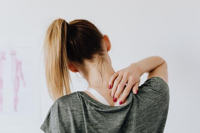 Mulher de costas com mão na nuca de cabelo amarrado