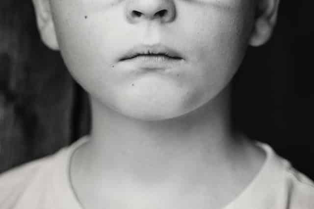 Meio rosto de criança com a boca fechada em foto preta e branca