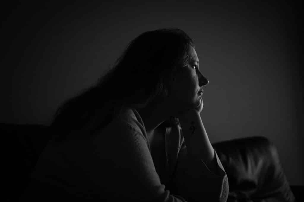 Mulher olhando apra frente em um quarto escuro