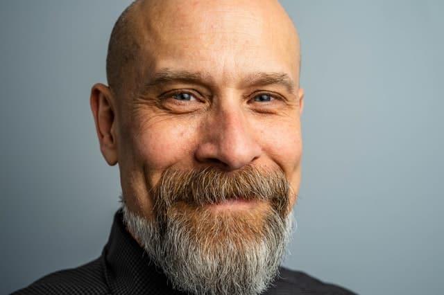Homem de frente sorrindo careca com barba