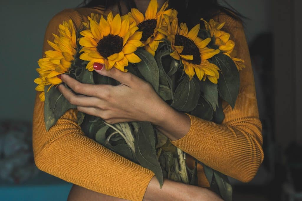 Mulher abraçando girassóis