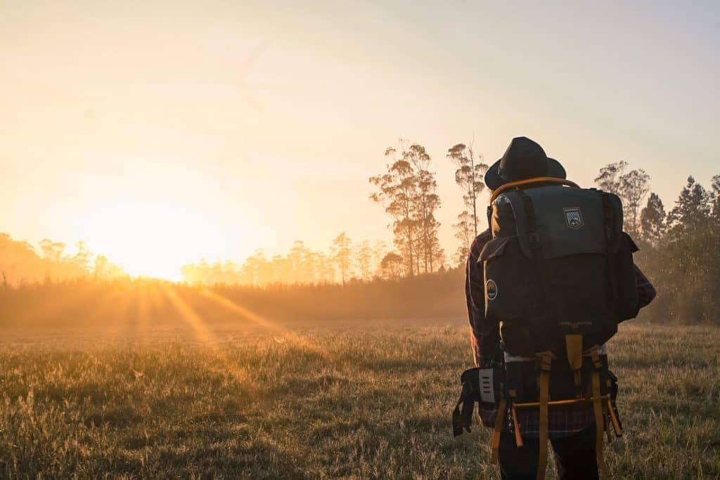 Pessoa com uma mochila grande nas costas em um campo olhando o pôr do sol.