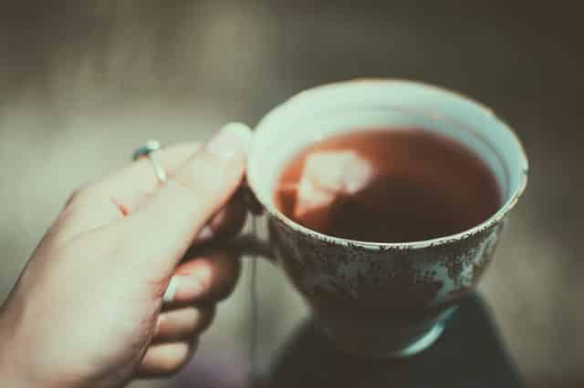 Mão branca feminina segurando xícara de chá.