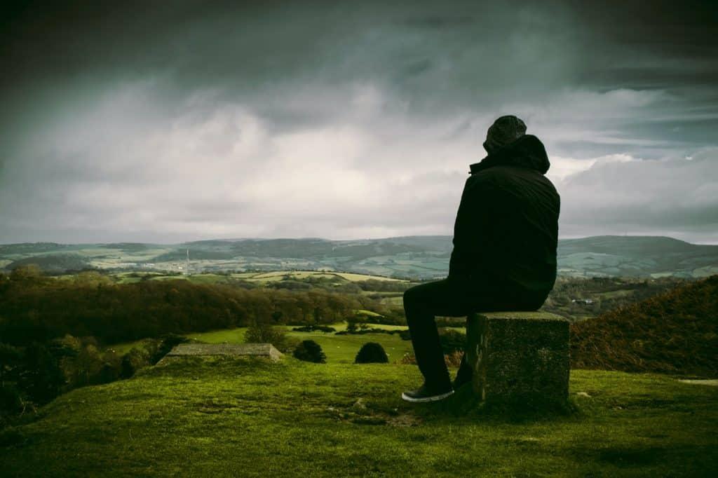 Homem sentado em um monte olhando a paisagem à sua frente.