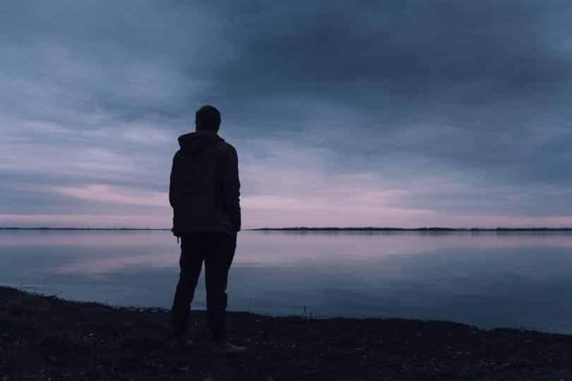 Homem em frente ao mar olhando para o lado