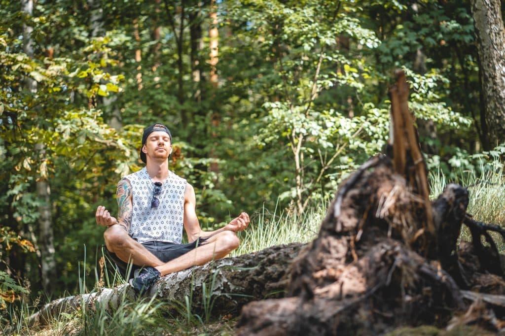 Homem meditando sentado na natureza.