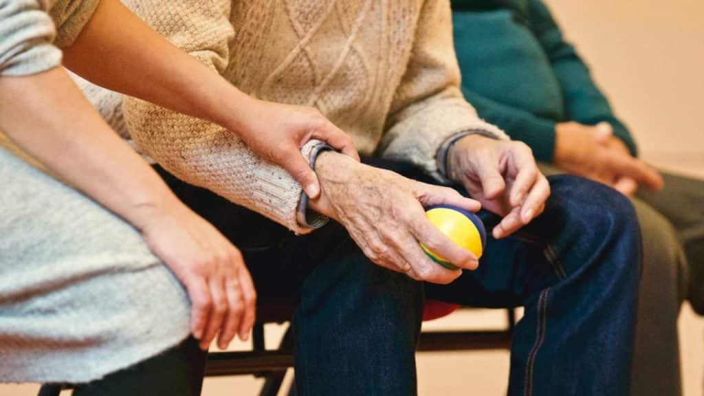 Uma senhora segurando uma pequena bola em uma de suas mãos, que está sendo apoiada pela mão de outra mulher.