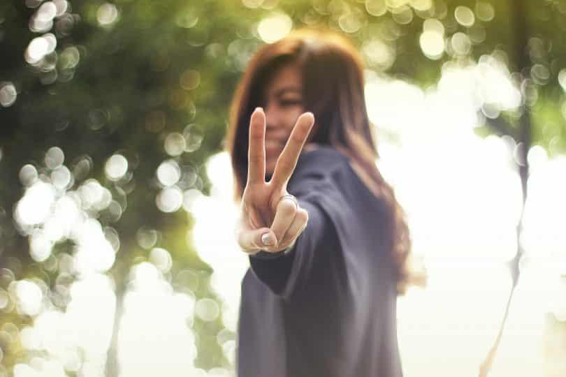 Mulher fazendo simbolo com os dedo de paz