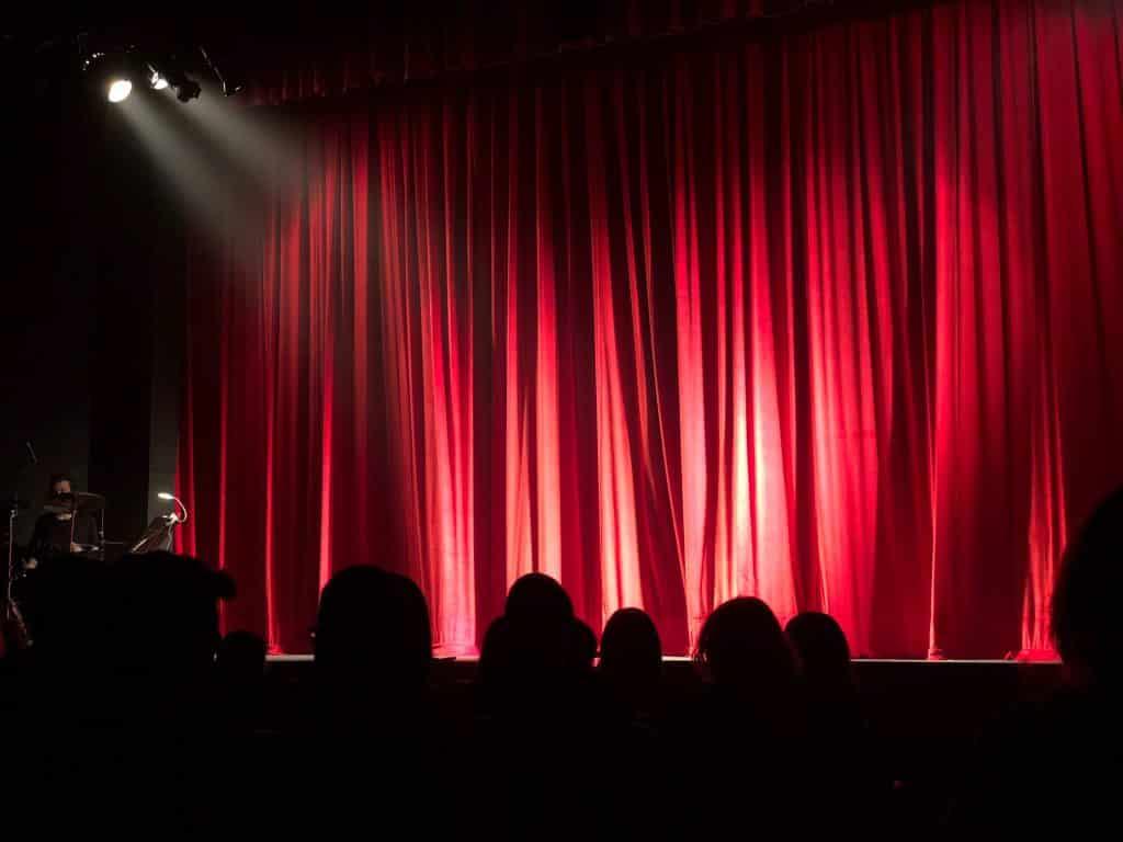 Teatro com as luzes no palco e cortina fechada