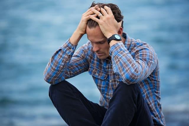 Homem sentado com mãos na cabeça com expressão de ansiedade e mar ao fundo