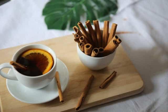 Chá de canela numa xícara branca e pote com canela em pau ao lado.