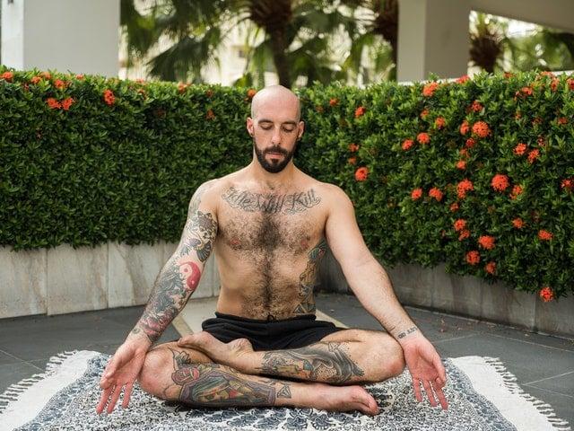 Homem sentado em posição de lótus meditando