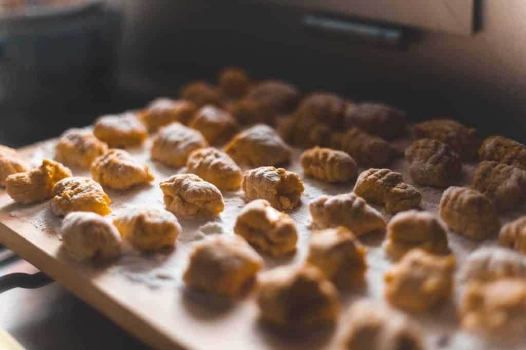 Muitas bolinhas de nhoque em cima de uma tábua com farinha.