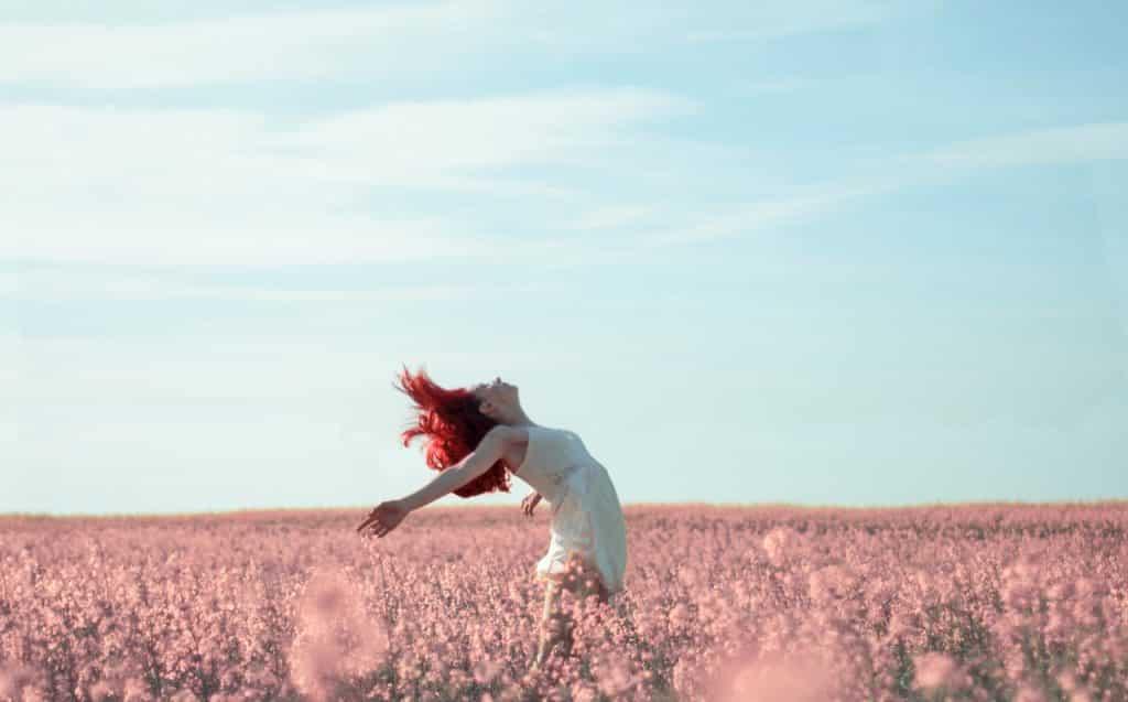 Mulher em um campo de flores com braços abertos.