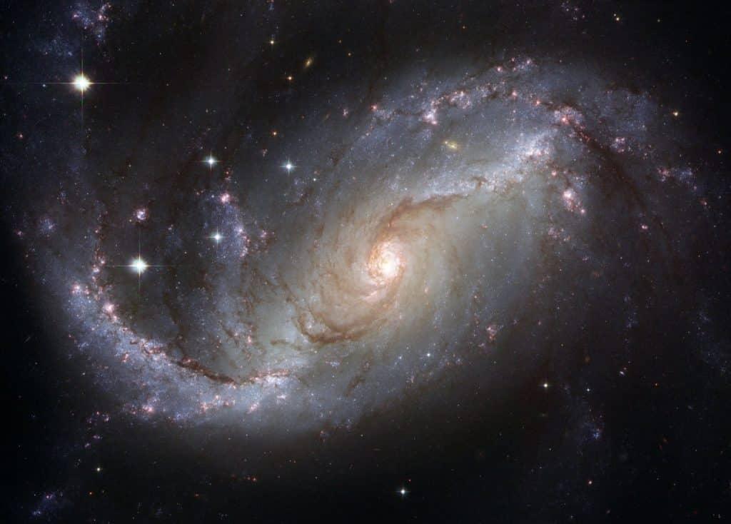 Galáxia em tons de bege, azul claro e roxo.