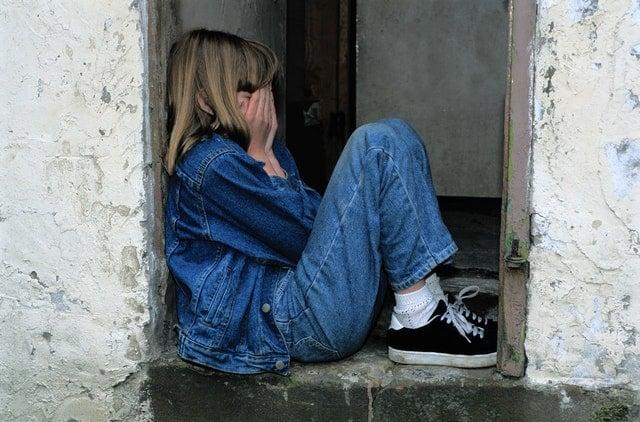 Garota com mãos no rosto encolhida em janela sozinha