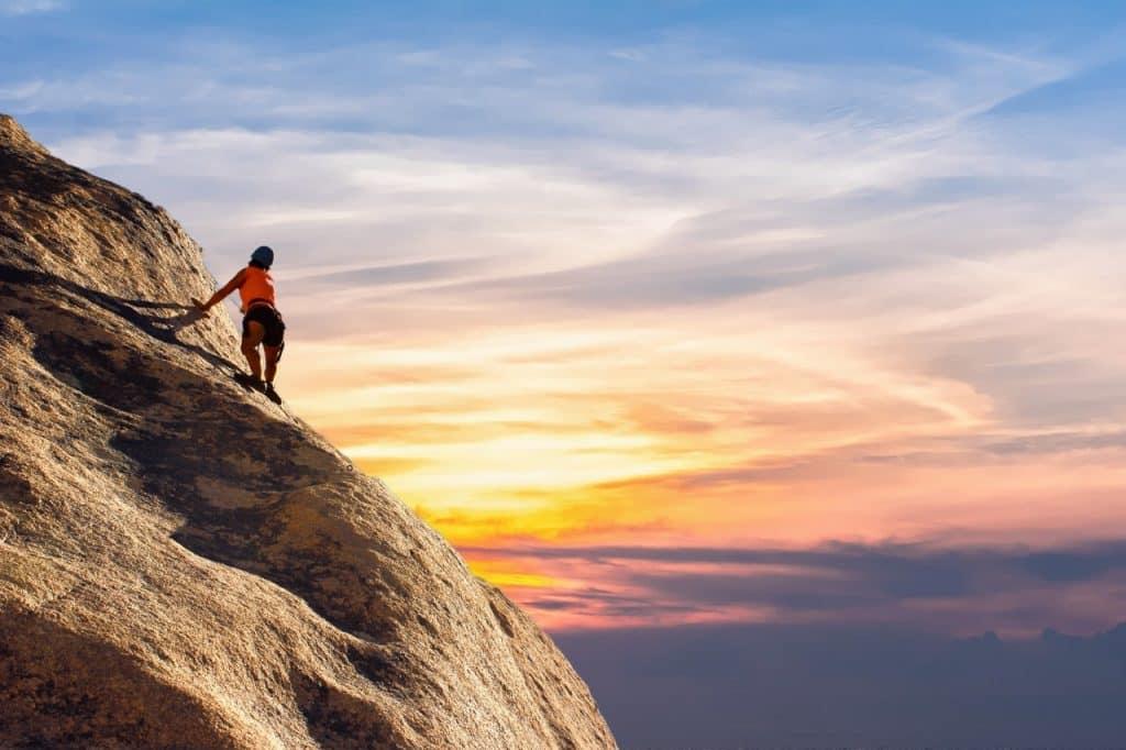 Pessoa escalando uma rocha íngreme, ao pôr do sol.