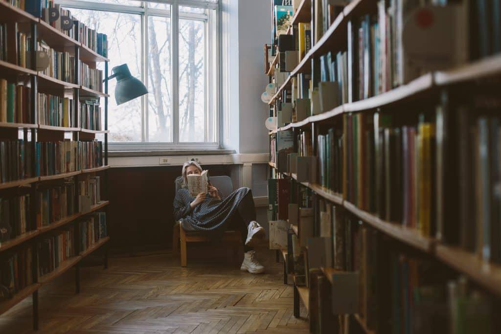 Mulher sentada em uma poltrona lendo um livro na biblioteca