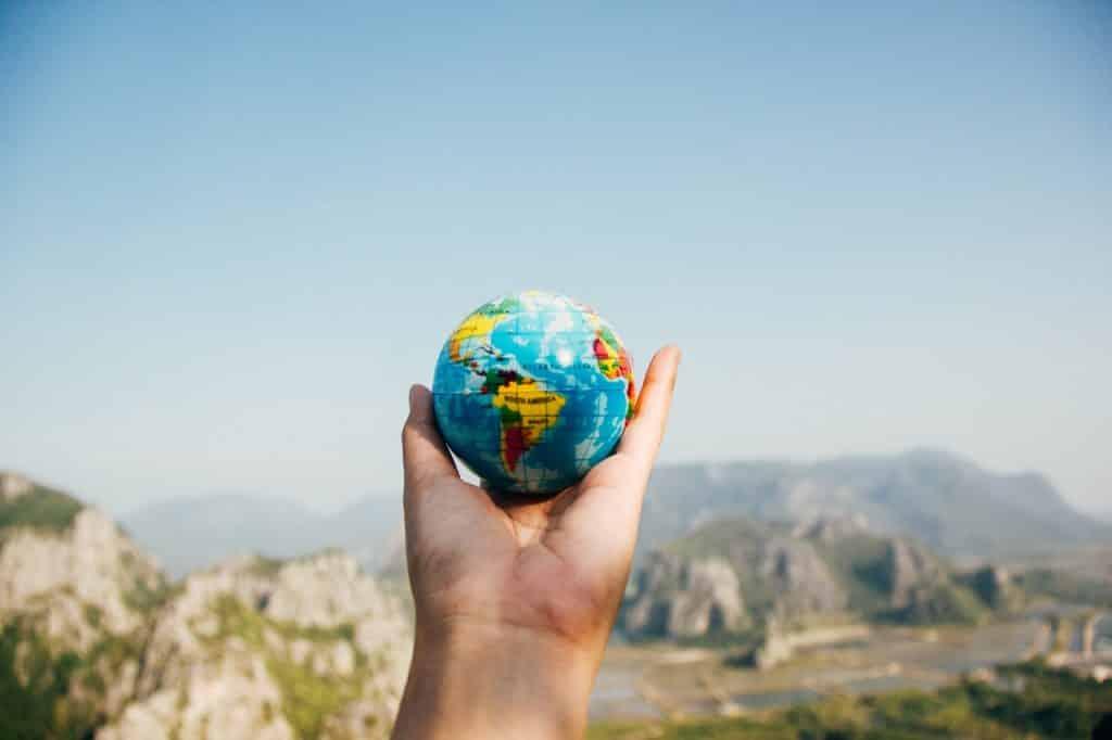 Mão branca segurando pequeno globo terrestre com montanhas ao fundo.