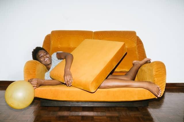 Mulher deitada em sofá com almofada no colo sorrindo