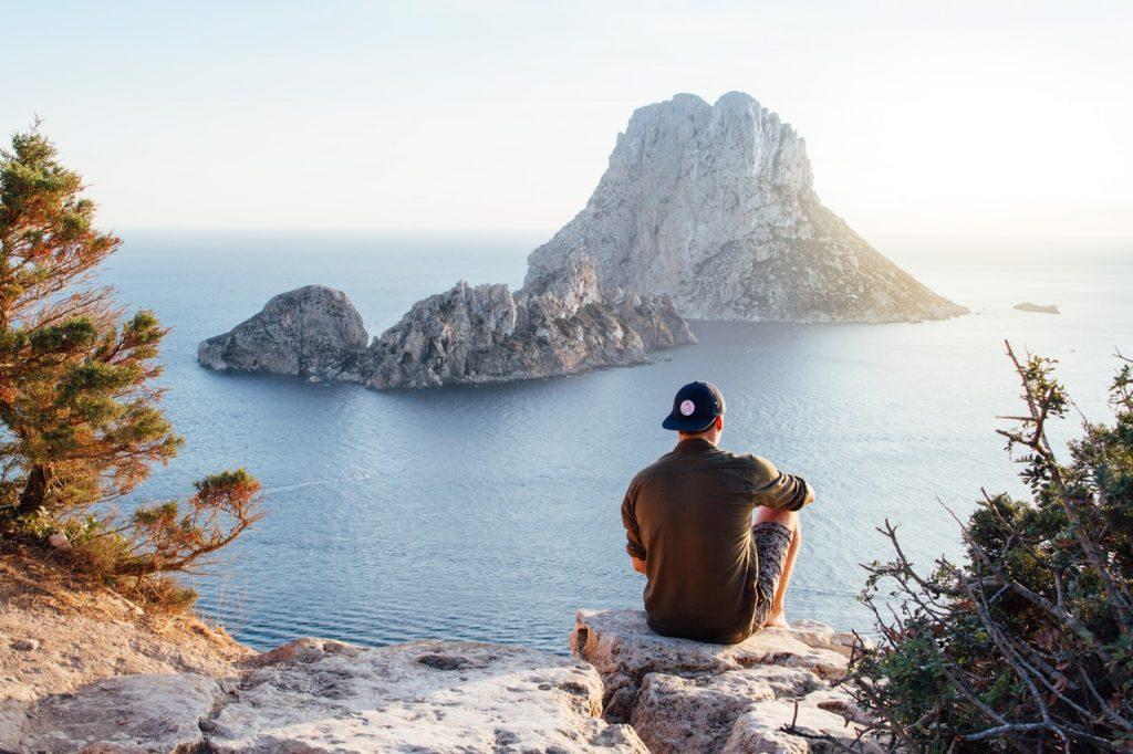 Homem sentado de costas numa pedra, usando boné preto para trás e camiseta verde, observando a praia.