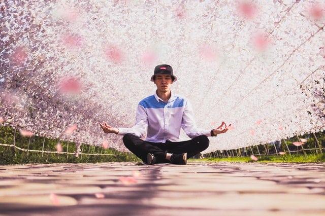 Homem sentado em posição de lótus com arco de flores ao fundo