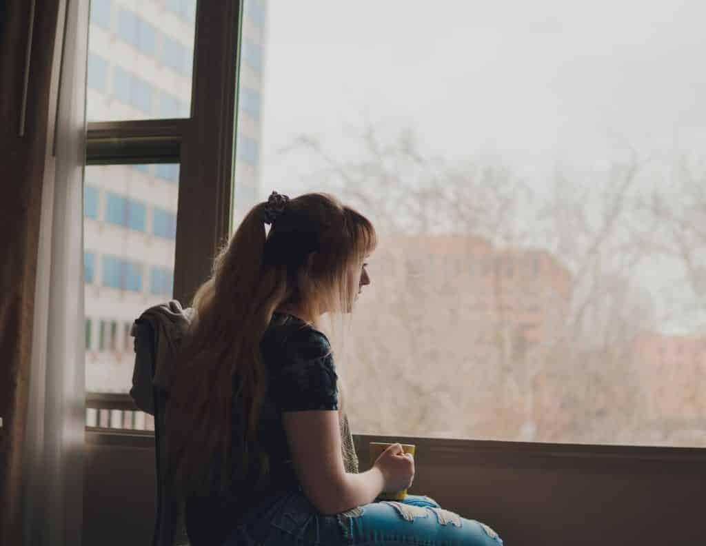 Mulher olhando para fora da janela e segurando uma xícara