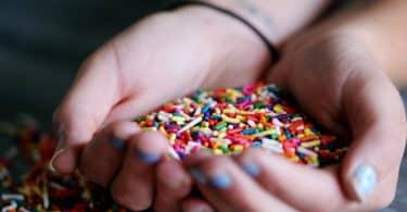 Mulher pegando com as duas mãos granulado colorido