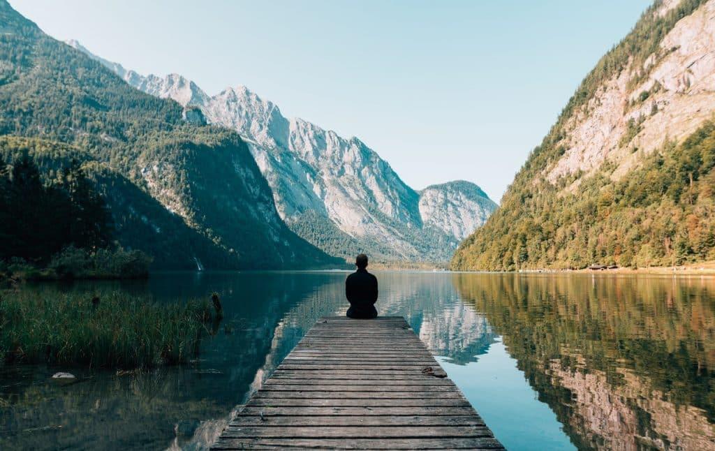 Homem sentado em um píer sobre um rio, em frente a uma paisagem montanhosa.