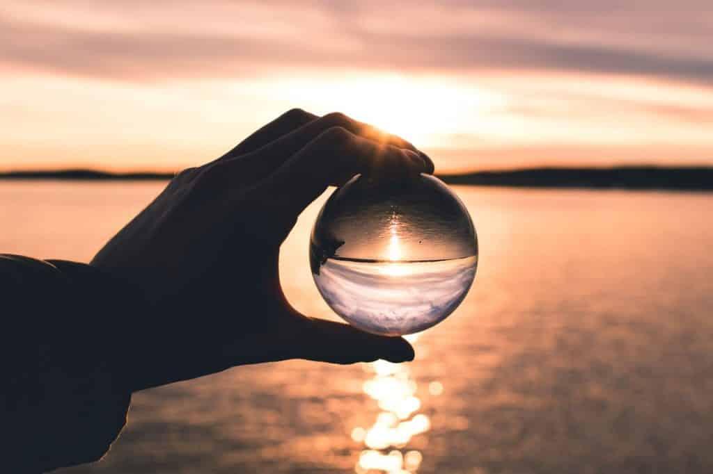 A mão de uma pessoa segurando uma bola transparente que reflete o mar e o céu.
