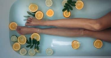 Mulher deitada na banheira com folhas e laranjas em rodelas