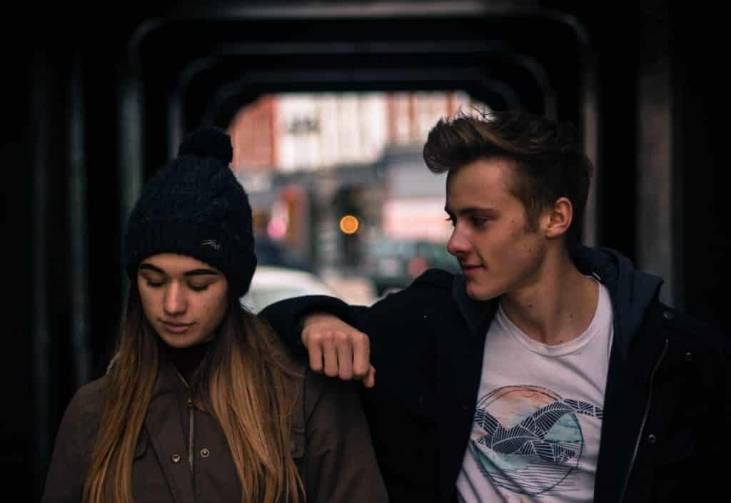 Casal andando lado a lado: a menina está olhando para baixo e o menino está apoiado no ombro dela e olhando para ela.