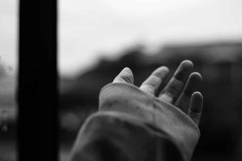 Mulher com a mão aberta em direção ao céu