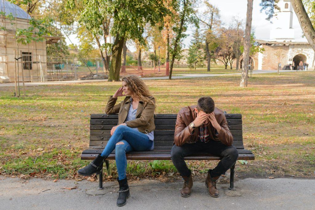 Uma mulher e um homem sentados em um banco de uma praça demonstrando desconforto pós briga.