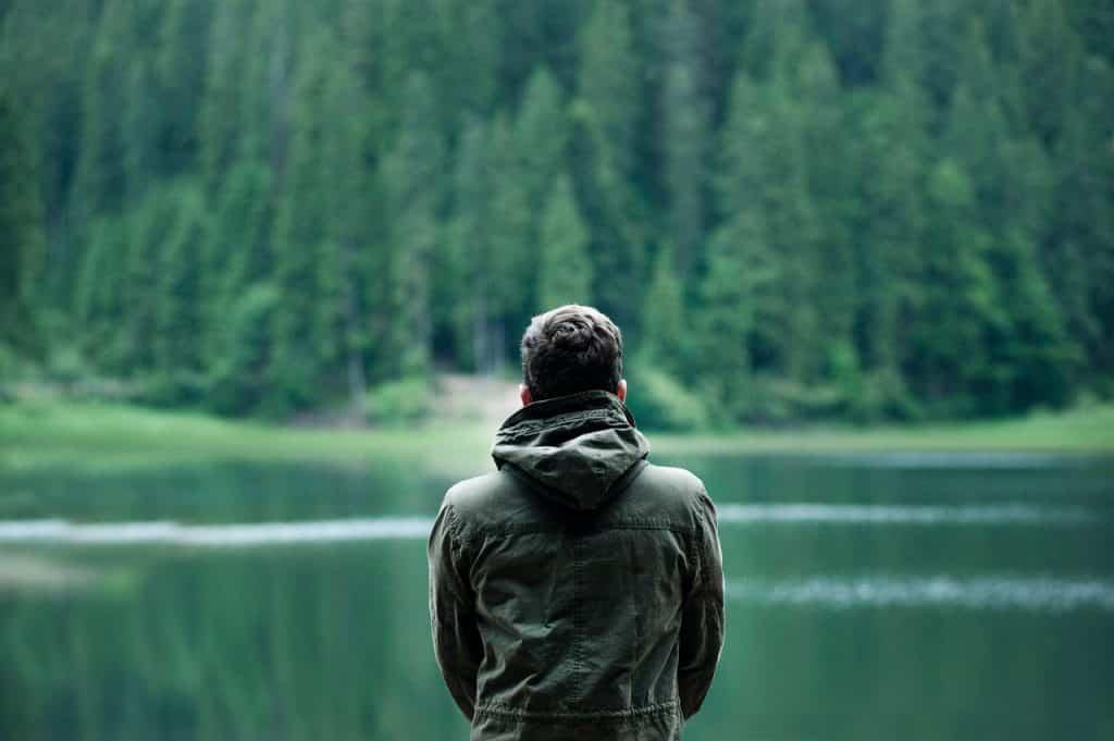Homem de costas sozinho em frente a um lago e muitas árvores.