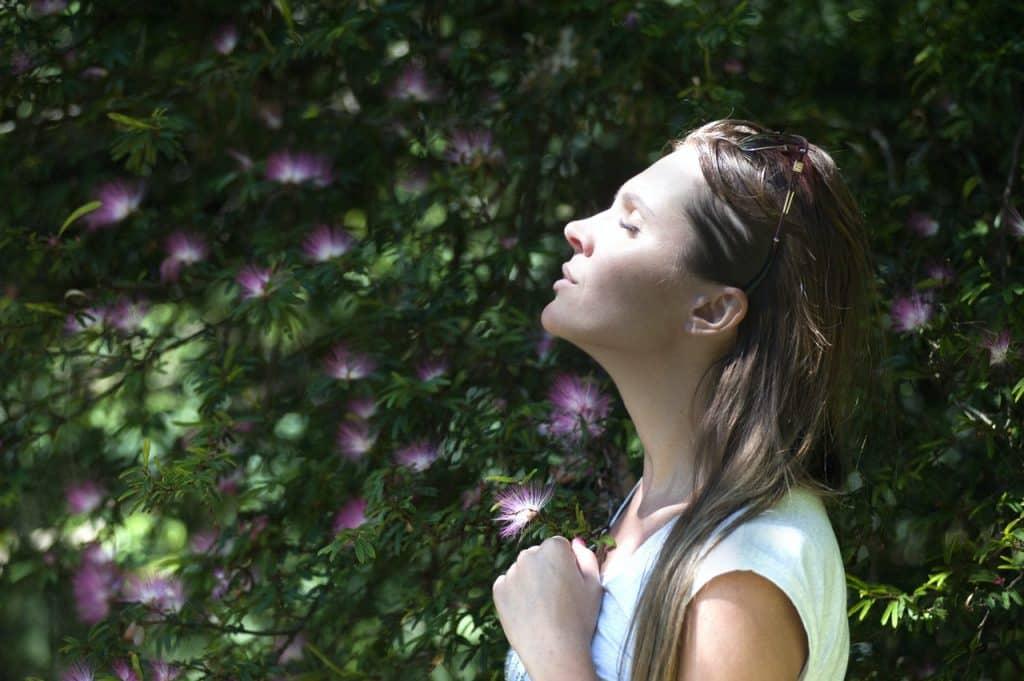 Mulher de perfil com olhos fechados, mão fechada no peito com a cabeça inclinada para cima em meio a uma árvore de folhas verdes e flores rosas.