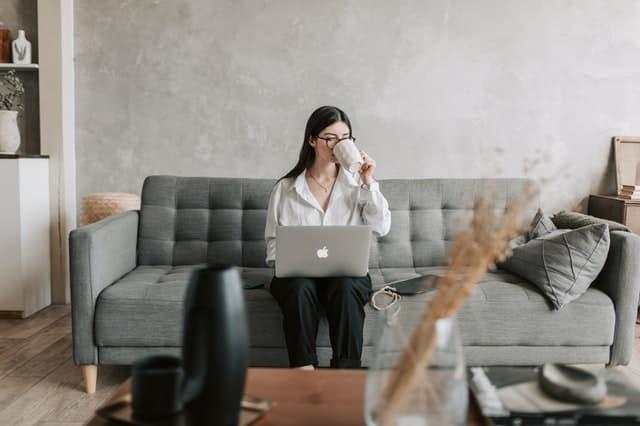 Mulher sentada no sofá trabalhando com o notebook no colo tomando café