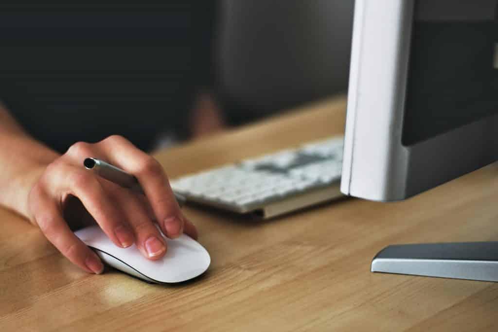 Mulher com a mão no mouse do computador