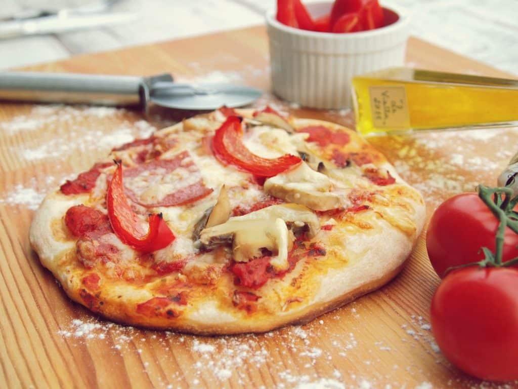 Imagem de uma linda e saborosa pizza de cogumelo com queijo e tomates.