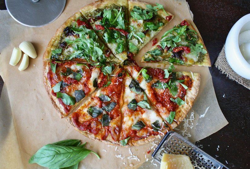 Imagem de uma linda e saborosa pizza vegetariana já fatiada. Ao lado dela alguns ingredientes como: manjericão, alho e queijo.