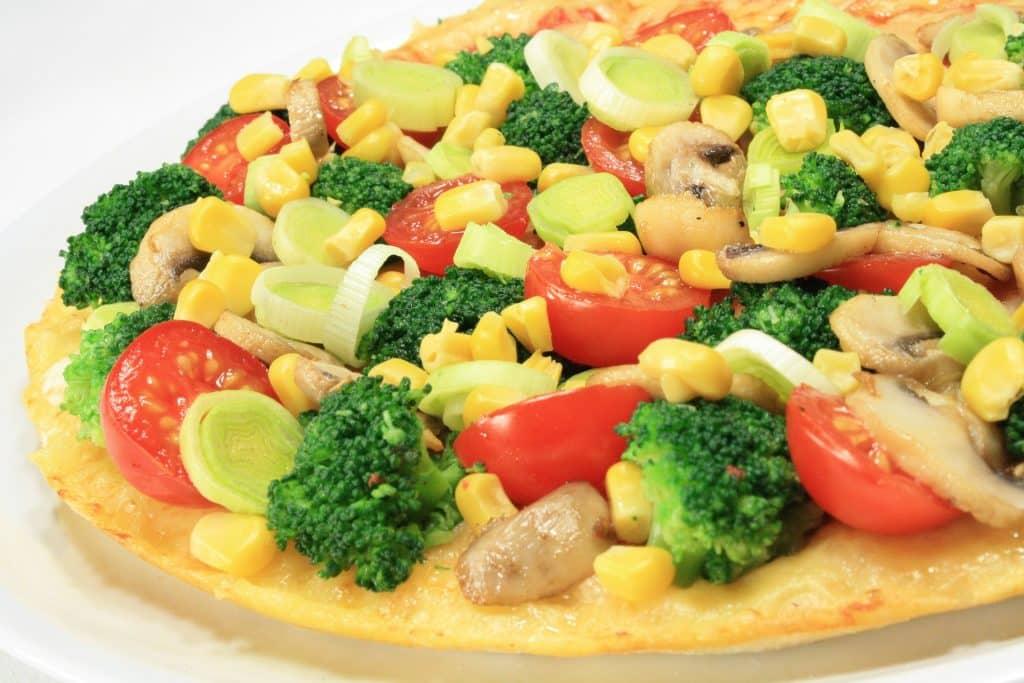 Imagem de uma pizza de brócolis com milho e outros ingredientes como tomate e alho poró.