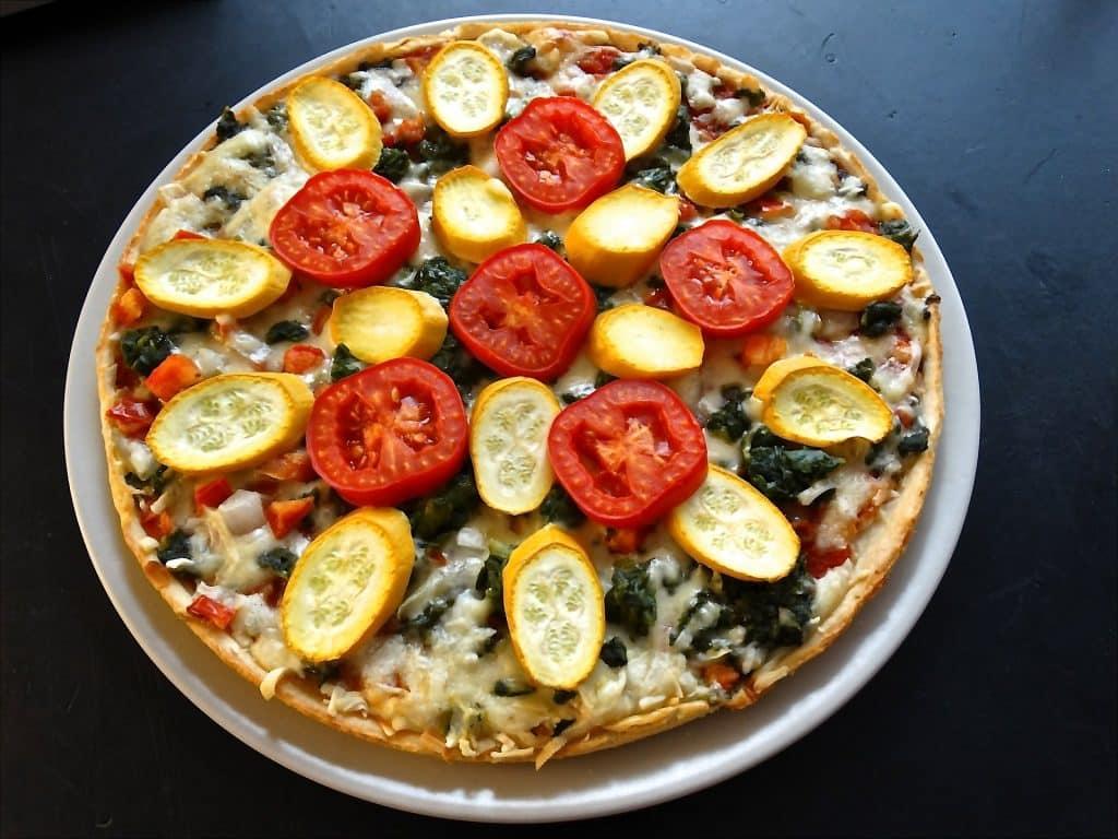Imagem de uma pizza vegetariana feita com diversos ingredientes e pronta para ser degustada.