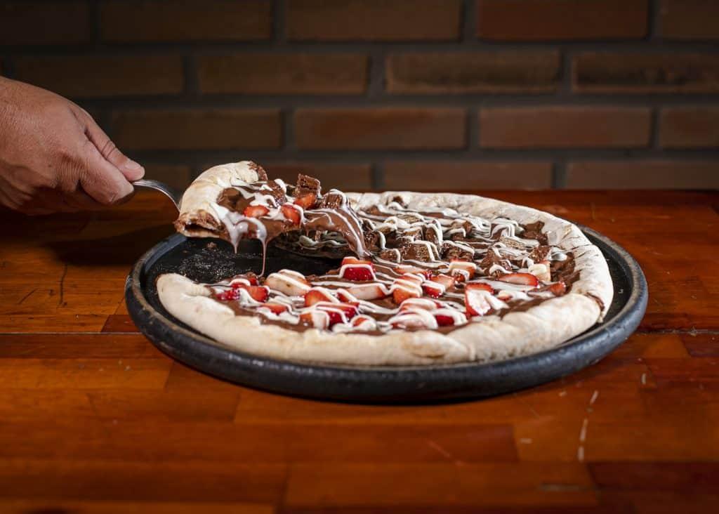 Imagem de uma pizza doce no sabeor de chocolate com morango. Ela está sendo cortada e pronta para ser servida.