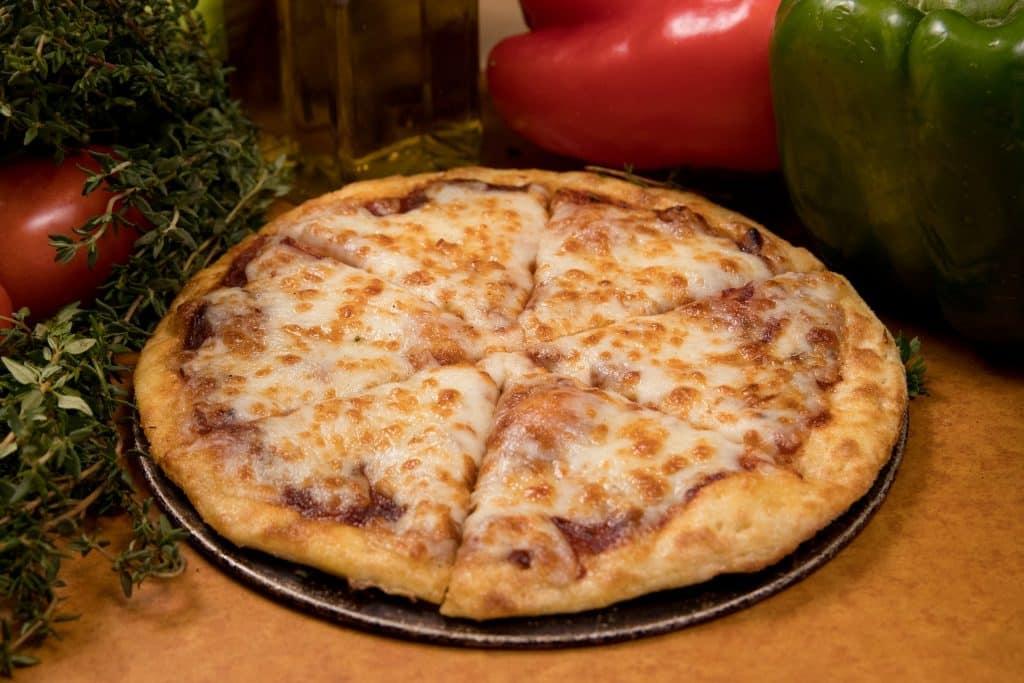 Imagem de uma linda e saborosa pizza de 4 queijos já assada e pronta para ser apreciada.