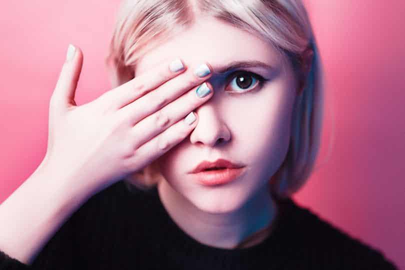 Imagem do rosto de uma jovem. Ela tampa um dos seus olhos. Suas unhas estão pintadas de cores diferentes de esmate.