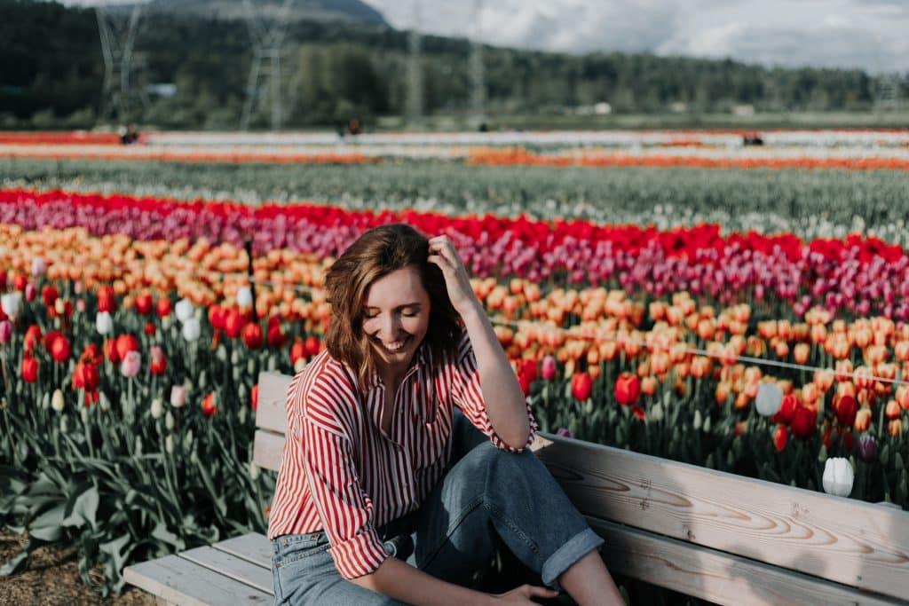 Mulher branca sentada num banco em frente a um jardim de tulipas.