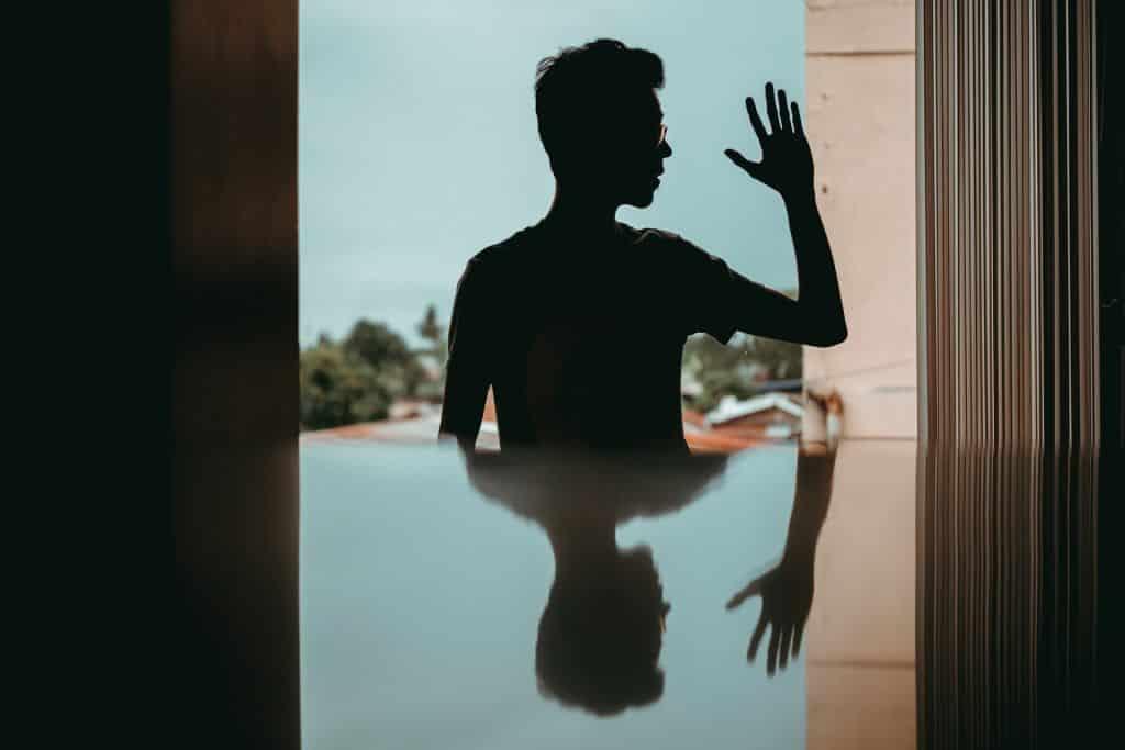 Silhueta de homem com a mão levantada com reflexo abaixo.