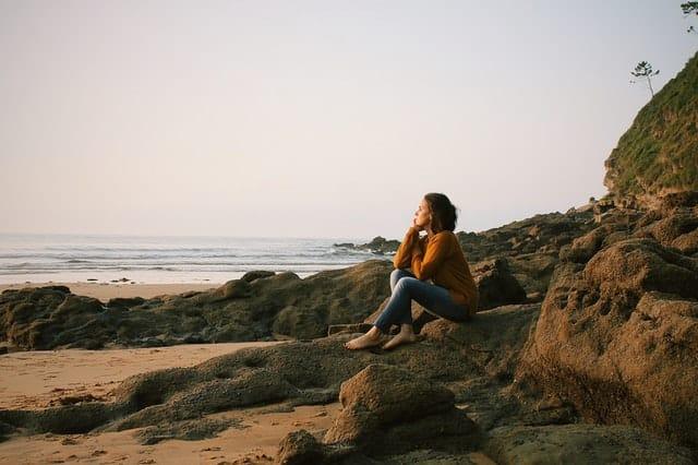 Mulher sentada à beira da praia, olhando para frente com expressão pensativa
