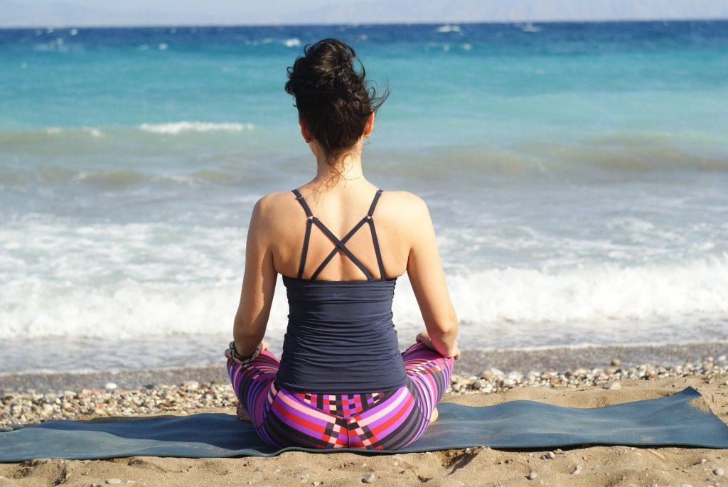 Imagem de uma mulher sentada e fazendo a sua meditação de frente para o mar.